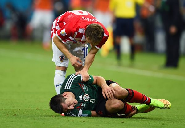RECIFE, BRAZIL - JUNE 23:  Hector Herrera of Mexico lies on the pitch as Luka Modric of Croatia stands over during the 2014 F