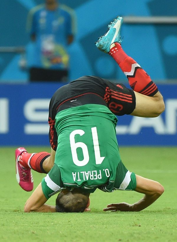 Mexico's forward Oribe Peralta falls on the pitch during a Group A football match between Croatia and Mexico at the Pernambuc