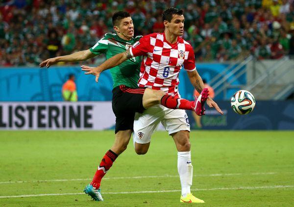 RECIFE, BRAZIL - JUNE 23:  Oribe Peralta of Mexico challenges Dejan Lovren of Croatia during the 2014 FIFA World Cup Brazil G