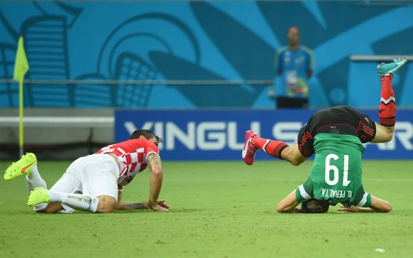 Mexico's forward Oribe Peralta (R) and Croatia's defender Dejan Lovren fall on the pitch during a Group A football match betw