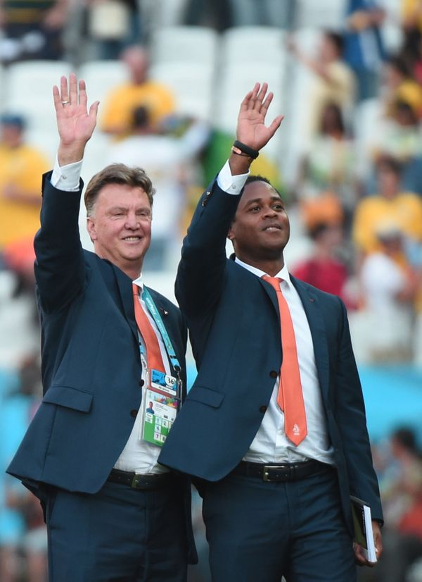 Netherlands' coach Louis van Gaal (L) and his assistant Patrick Kluivert celebrate after the Group B football match between N