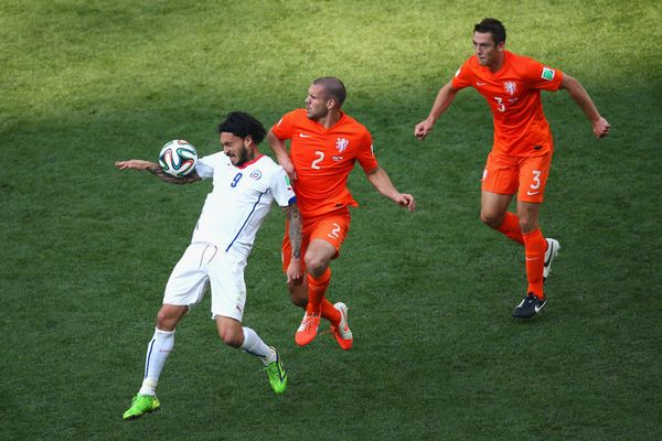 SAO PAULO, BRAZIL - JUNE 23: Mauricio Pinilla  of Chile and Ron Vlaar of the Netherlands compete for the ball during the 2014