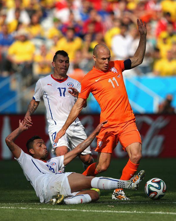 SAO PAULO, BRAZIL - JUNE 23:  Felipe Gutierrez of Chile tackles Arjen Robben of the Netherlands during the 2014 FIFA World Cu