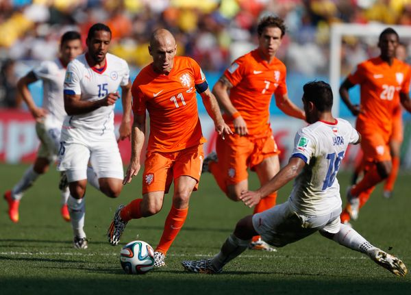 SAO PAULO, BRAZIL - JUNE 23:  Arjen Robben of the Netherlands controls the ball as Gonzalo Jara of Chile gives chase during t