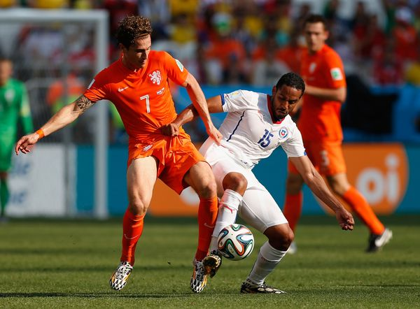 SAO PAULO, BRAZIL - JUNE 23:  Daryl Janmaat of the Netherlands and Jean Beausejour of Chile compete for the ball during the 2