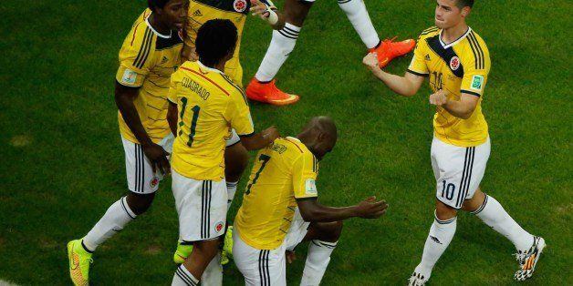 Colombia's midfielder James Rodriguez (R) is mobbed by teammates as he celebrates his second goal during the Round of 16 foot