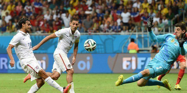 US forward Chris Wondolowski (L) shoots past Belgium's goalkeeper Thibaut Courtois during a Round of 16 football match betwee