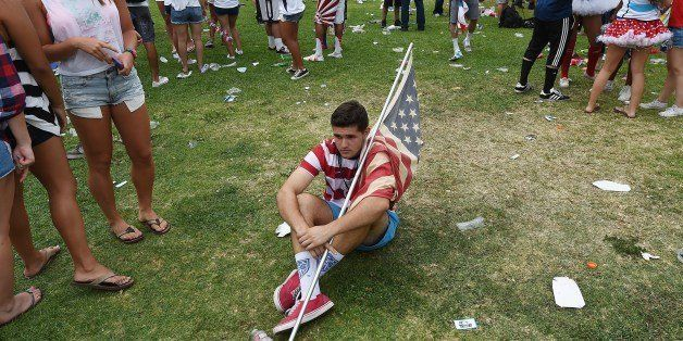 A soccer fan sits on the ground during a viewing party at Veteran's Park in Redondo Beach, California July 1, 2014 after Belg