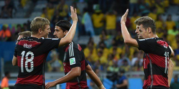 Germany's forward Miroslav Klose (R) celebrates with teammates after scoring during the semi-final football match between Bra