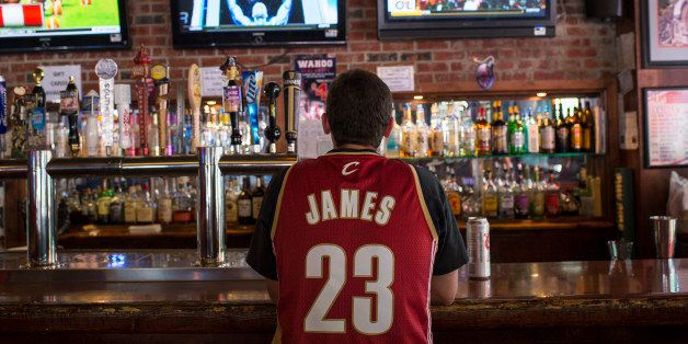 CLEVELAND, OH - JULY 11: A Cleveland Cavaliers fan wearing a Lebron James jersey watches news coverage of LeBron James return