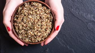 Healthy cooked quinoa in woman hand . Superfood background