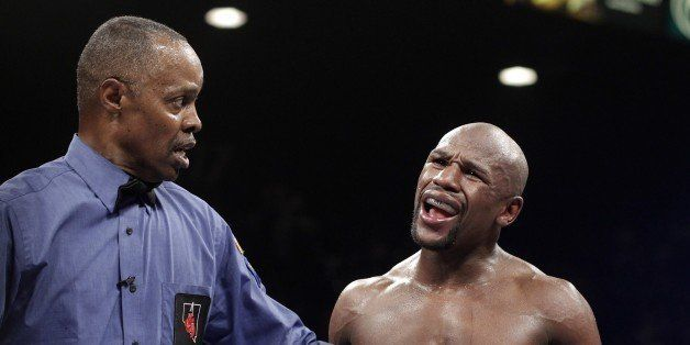 Referee Kenny Bayless holds back Floyd Mayweather Jr. of the US as he reacts accusing Marcos Maidana of Argentina on Septembe