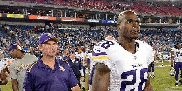 Minnesota Vikings running back Adrian Peterson (28) and head coach Mike Zimmer, left, walk onto the field after beating the T