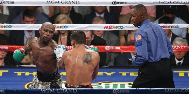 LAS VEGAS, NV - SEPTEMBER 13: Floyd Mayweather Jr. (L) jabs at Marcos Maidana as referee Kenny Bayless watches, during their
