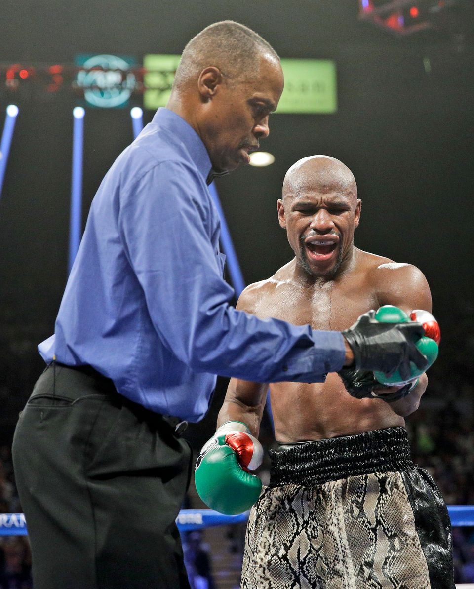 Floyd Mayweather speaks to referee Kenny Bayless, left, after he claimed that Marcos Maidana bit his hand during their title