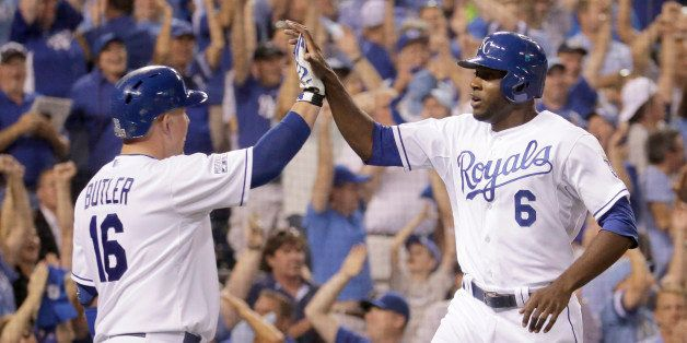 Kansas City Royals' Lorenzo Cain (6) and Billy Butler (16) celebrate after Cain scored on a single by Eric Hosmer during the