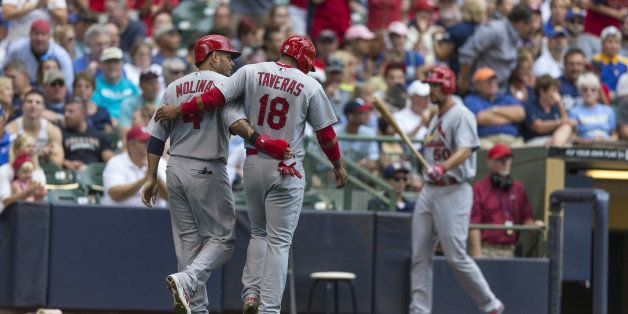 MILWAUKEE, WI - SEPTEMBER 7: Oscar Taveras #18 of the St. Louis Cardinals and teammate Yadier Molina #4 walk off the field af