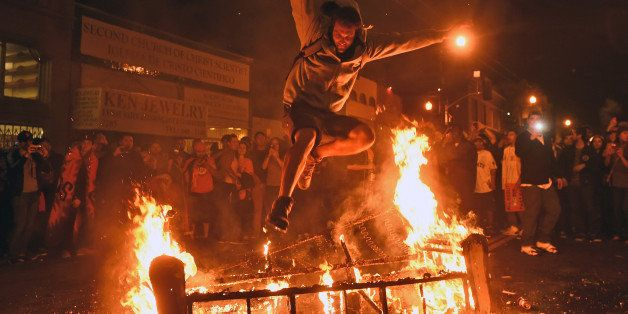 A man jumps over some debris that has been set on fire in the Mission district after the San Francisco Giants beat the Kansas
