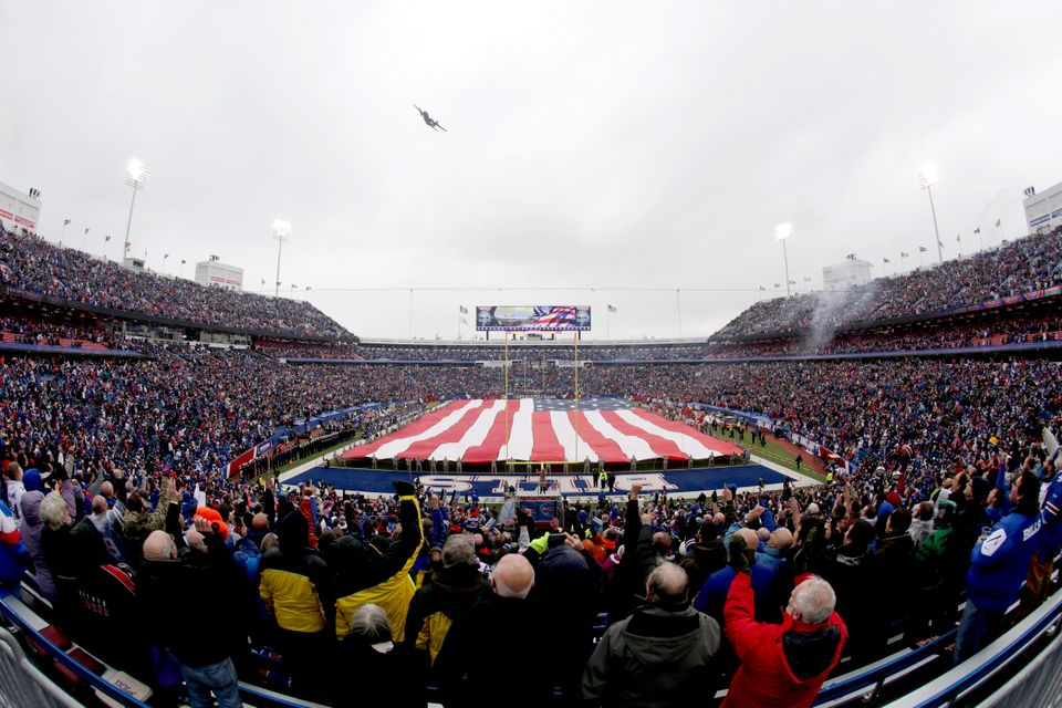 In this photo taken with a fisheye lens, a military aircraft flies over a large United States flag placed on the field before