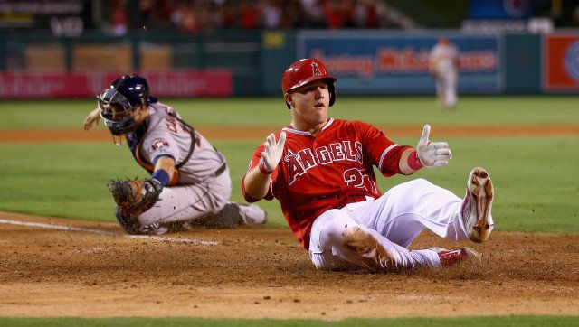 ANAHEIM, CA - SEPTEMBER 12:  Mike Trout #27 of the Los Angeles Angels of Anaheim slides safely past catcher Jason Castro #15