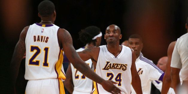 LOS ANGELES, CA - NOVEMBER 23:  Kobe Bryant #24 of the Los Angeles Lakers celebrates with teammate Ed Davis #21 during the fi