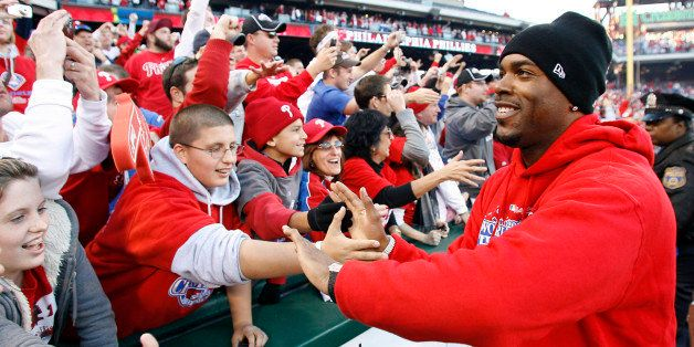 Philadelphia Phillies' Jimmy Rollins hi-fives fans lining the field at Citizen's Bank park at the end of the celebration of t