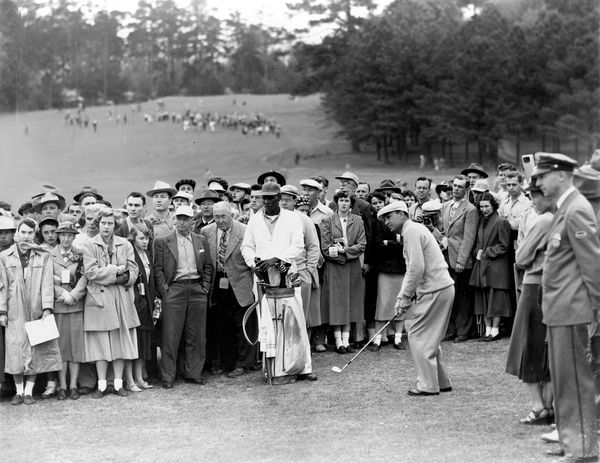 Ben Hogan, of Ft. Worth, Texas, chips out of the crowd to the 7th green after his approach shot rolled from the green and sto