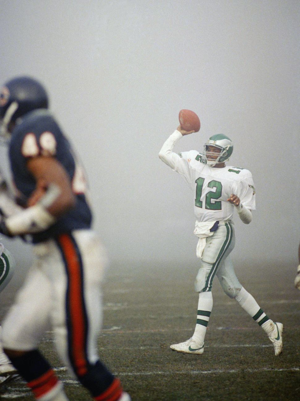 Philadelphia Eagles quarterback Randall Cunningham (12) comes out of the fog to throw a pass during action in their semi-fina
