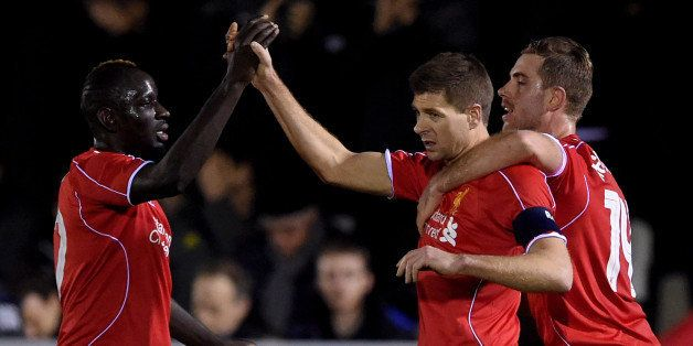 KINGSTON UPON THAMES, ENGLAND - JANUARY 05:  Steven Gerrard of Liverpool is congratulated by teammates Mamadou Sakho (L) and