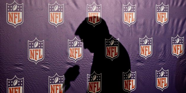 The shadow of NFL Commissioner Roger Goodell is cast on the NFL logo background as he pauses before answering a question from
