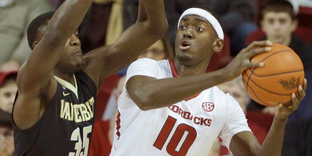 Arkansas' Bobby Portis (10) tries to pass around Vanderbilt's James Siakam (35), of Cameroon, in the first half of an NCAA co