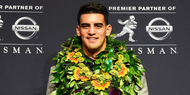 NEW YORK, NY - DECEMBER 13:  Oregon Ducks quarterback Marcus Mariota poses with the Heisman Trophy during a press conference