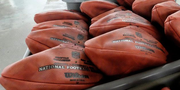 Official game balls for NFL football's Super Bowl XLIX sit in a bin before being laced and inflated at the Wilson Sporting Go