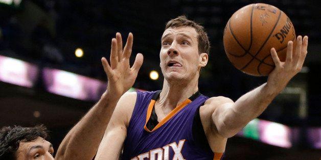 FILE - In this Jan. 6, 2015, file photo, Phoenix Suns' Goran Dragic attempts a layup over Milwaukee Bucks' Zaza Pachulia duri