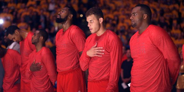 Los Angeles Clippers players listen to the national anthem wearing their warmup jerseys inside out to protest alleged racial
