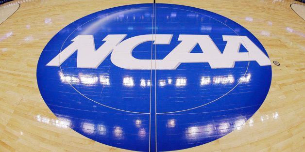 FILE - In this March 21, 2013, file photo, in this image taken with a fisheye lens, the NCAA logo is displayed at mid-court b