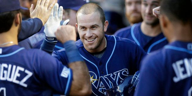 Tampa Bay Rays' Evan Longoria high-fives teammates in the dugout after hitting a solo home run in the first inning of a baseb