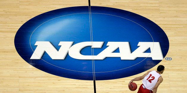 FILE - In this March 26, 2014, file photo, Wisconsin's Traevon Jackson dribbles past the NCAA logo during practice at the NCA