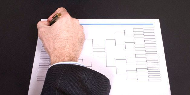 Closeup of a businessman's hand holding a pen completing tournament bracket