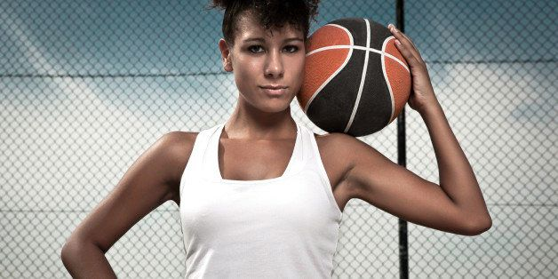 Portrait of female basketball player posing with basketball.