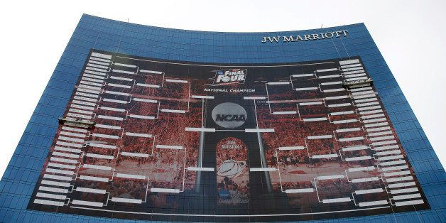 Workers add team names to a  2015 NCAA Division I Men's Basketball Championship bracket that is displayed on the side of th