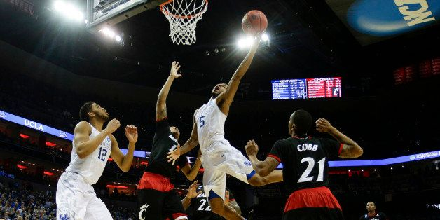 Kentucky's Andrew Harrison (5) drives in for the basket and a foul as the Wildcats defeated Cincinnati, 64-51, in the third r