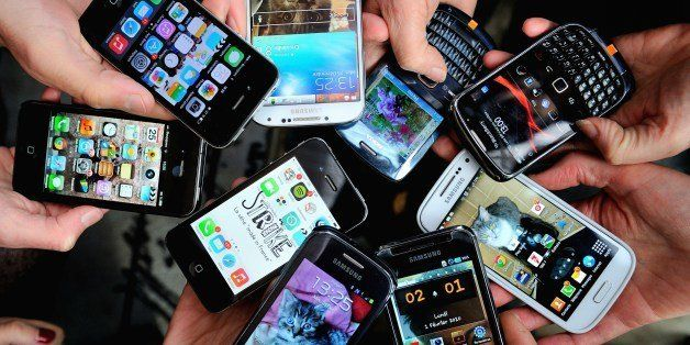 People show their smartphones on December 25, 2013 in Dinan, northwestern France.   AFP PHOTO / PHILIPPE HUGUEN        (Photo