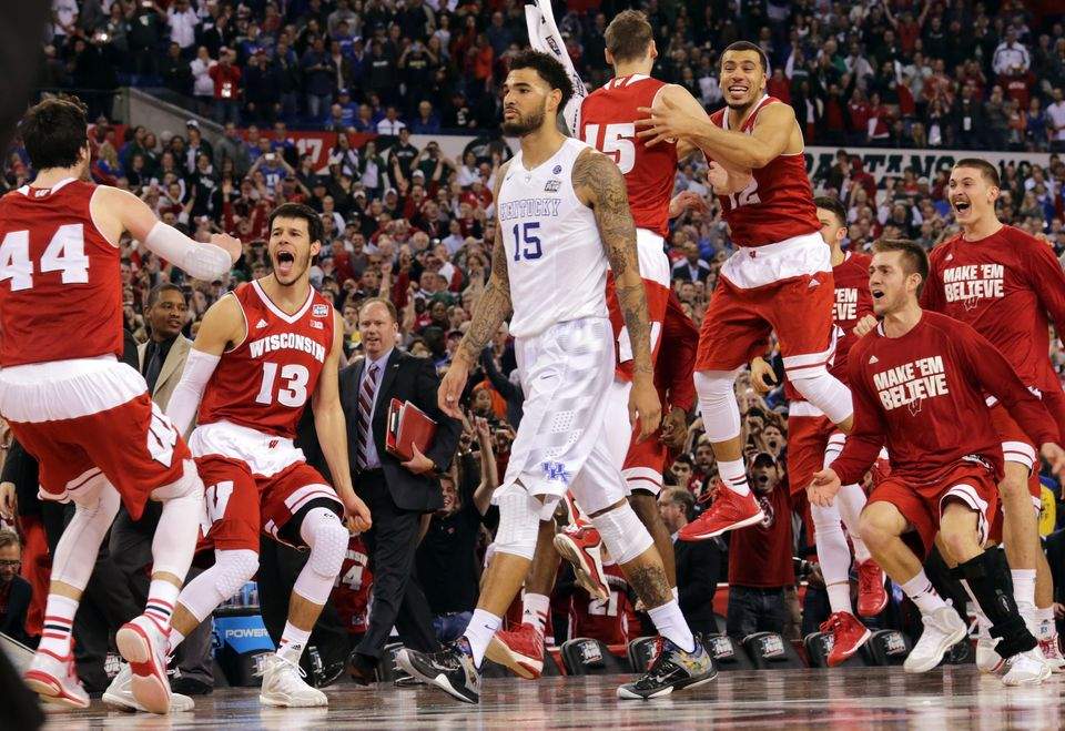 Wisconsin bench celebrates as Kentucky's Willie Cauley-Stein walks off after the NCAA Final Four tournament college basketbal