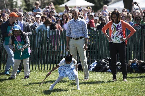 President Barack Obama and first lady Michelle Obama watch children during the annual Easter Egg Roll on the South Lawn of th