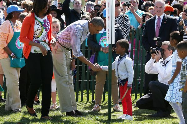 President Barack Obama (center) congratulates a participant during the White House Easter Egg Roll with first lady Michelle O