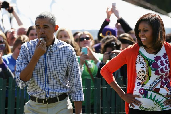 President Barack Obama blows a whistle to start the White House Easter Egg Roll as first lady Michelle Obama looks on.