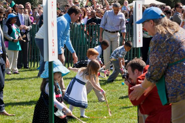 President Barack Obama watches as children participate in the White House Easter Egg Roll.