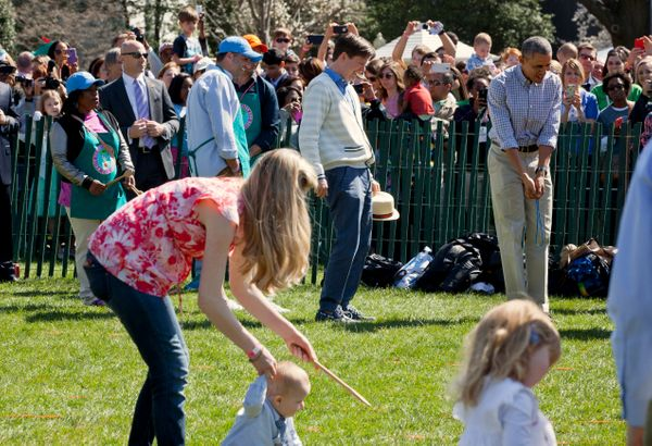 President Barack Obama watches children participate in the White House Easter Egg Roll.