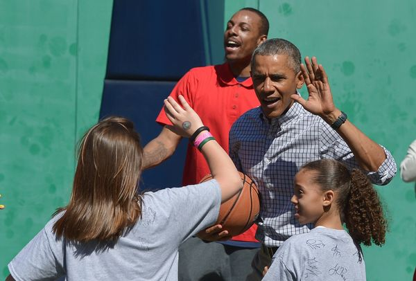 President Barack Obama high-fives a child while playing basketball during the annual Easter Egg Roll on the South Lawn of the
